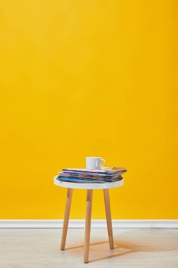 Little coffee table with journals and cup of coffee near yellow wall