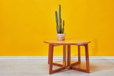 Cactus in flowerpot on little wooden table near yellow wall stock vector