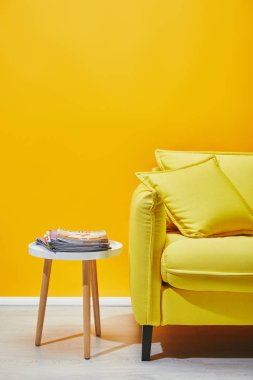 Sofa with pillows and little table with journals near yellow wall