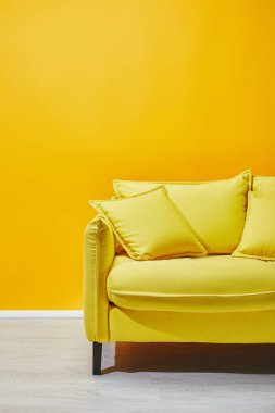 Sofa with pillows near bright yellow wall stock vector
