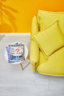 Sofa with pillows and coffee table with business magazines