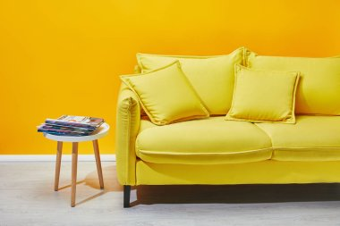 Sofa with pillows and coffee table with press near yellow wall