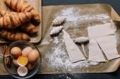 Fotografie Draufsicht auf Backpapier mit Teig für Croissants, Eier und Zimt auf Oberfläche
