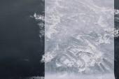 Fotografie Draufsicht des Mehls mit Backpapier auf schwarzen Tisch