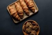 Draufsicht auf Tablett mit leckeren Croissants und Kekse in Schüssel auf schwarzen Tisch