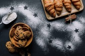 Fotografie flat lay with croissants and cookies on table covered by flour with stars as big dipper constellation