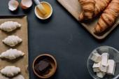 Fotografia vista elevata di ingredienti, impasto per cornetti sul vassoio, tuorlo con pennello sulla tabella nera