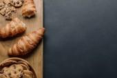 pohled shora croissanty a sušenky s kousky čokolády v misce na černý stůl