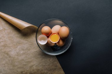 top view of eggs in bowl and baking paper on black table