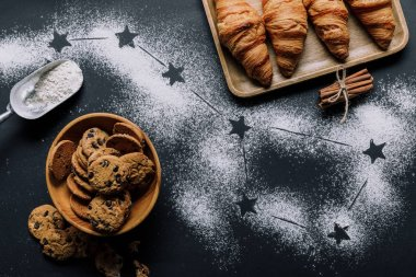 flat lay with croissants and cookies on table covered by flour with stars as big dipper constellation