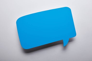 top view of empty blue speech bubble on grey background