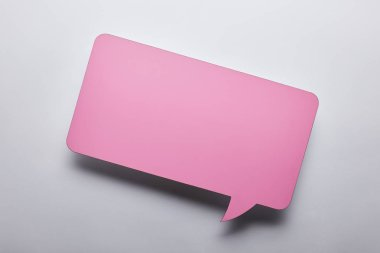 top view of empty pink speech bubble on grey background