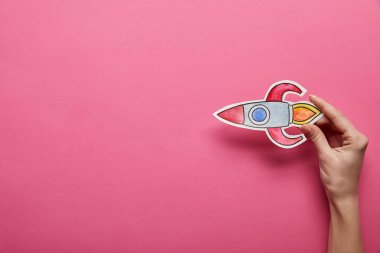 elevated view of flying rocket on pink background