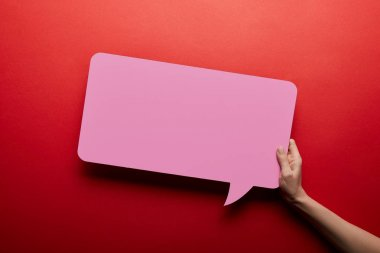 top view of empty speech bubble in pink color on red background