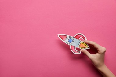 top view of hand holding rocket on pink background