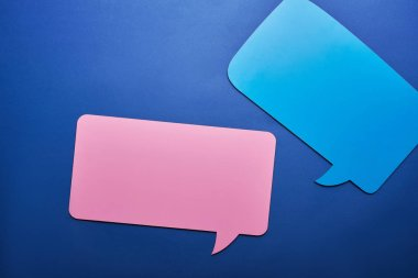top view of empty blue and pink speech bubbles on blue background