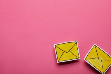 top view of two yellow message icons on pink background