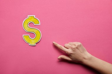 Top view of finger pointing at dollar sign on pink background stock vector