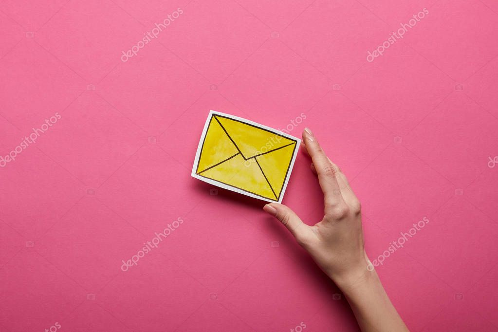 top view of hand holding yellow message sign on pink background