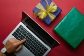 Top view of man pushing button on laptop keyboard near gifts on red background