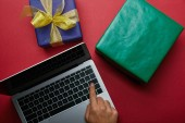 Top view of woman pushing button on laptop keyboard near wrapped gifts on red background