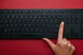Pohled shora ženy stlačením tlačítka na černé počítačovou klávesnici na červeném pozadí