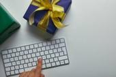 Oříznutý pohled člověka stlačením tlačítka na klávesnici počítače poblíž barevné dárky na šedém pozadí