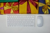 Top view of gifts near computer keyboard and computer mouse on white background