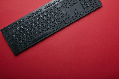 Top view of black computer keyboard on red background with copy space stock vector