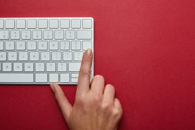 Cropped view of woman pushing button on computer keyboard on red background