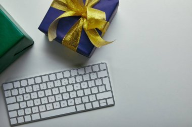 Cropped view of gifts near white computer keyboard on grey background stock vector