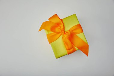 Top view of wrapped gift with orange bow isolated on grey background stock vector