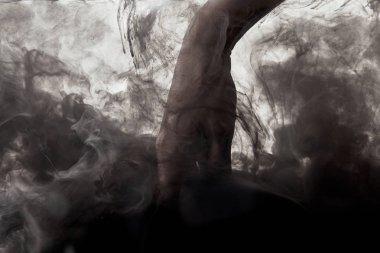hand in water with swirls of dark paint