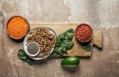 Draufsicht auf gesundes Müsli, Goji-Beeren, rote Linsen und Spinat auf Holzbrett mit rustikalem Hintergrund