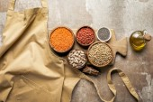 Photo flat lay of apron, legumes, goji berries and chia seeds on wooden board with rustic background