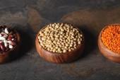 Fotografie Soja, Bohnen und Linsen in Holzschalen auf Tisch