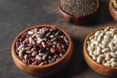 Vielzahl von Bohnen in Holzschalen mit Chia-Samen auf Tisch