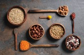 Photo top view of wooden bowls and spoons with superfoods, legumes and grains on table