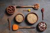 Fotografie top view of wooden bowls and spoons with superfoods, legumes and grains on table