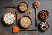 Fotografie flat lay of wooden bowls and spoons with superfoods, legumes and grains on table