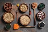 flache Lay hölzerne Schüsseln und Löffel mit Superfoods, Hülsenfrüchten und Getreide auf Tisch