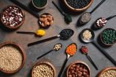 Draufsicht der hölzerne Schüsseln und Löffel mit Superfoods, Hülsenfrüchten und Getreide auf Tisch