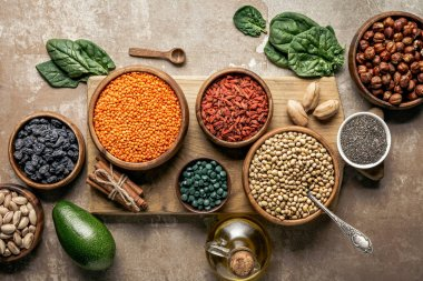 top view of wooden board with legumes, goji berries and healthy ingredients with rustic background