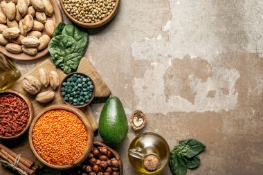 top view of superfoods, legumes, olive oil and healthy ingredients on rustic background with copy space