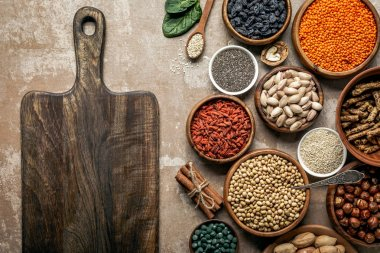 top view of wooden board, superfoods, legumes and healthy ingredients on rustic background