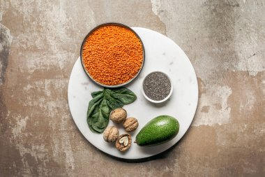 chia seeds, avocado, red lentils and walnuts on plate with textured rustic background
