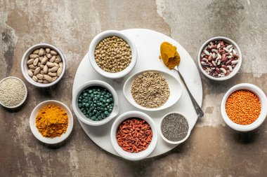 top view of superfoods, nuts and legumes on textured rustic background