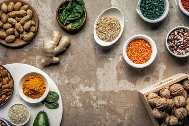 flat lay of spices, legumes, superfoods and nuts on textured rustic background with copy space