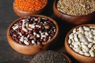 variety of beans, lentils and oat groats in wooden bowls on table