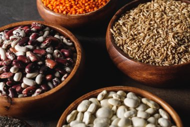 variety of beans in wooden bowls with oat groats on table
